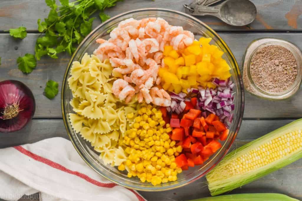 overhead view of a clear bowl filled with bow tie pasta, corn, red bell pepper pieces, red onion, yellow bell peppers, and shrimp broken down by ingredient