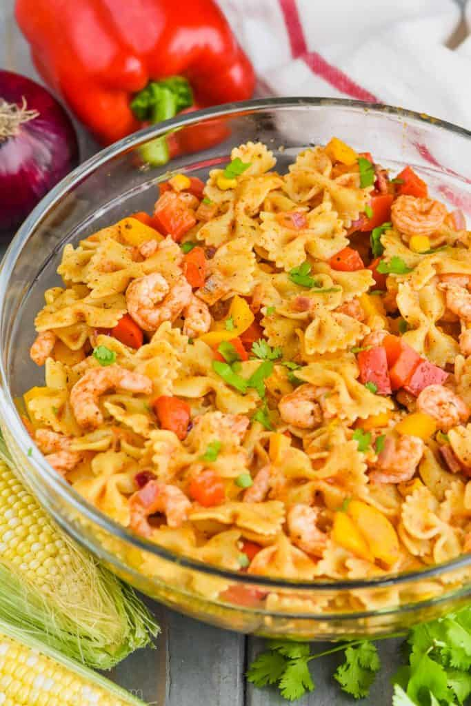 a clear bowl filled with shrimp fajita pasta salad, two ears of corn in front of it, some cilantro and a red bell pepper and a red onion behind it