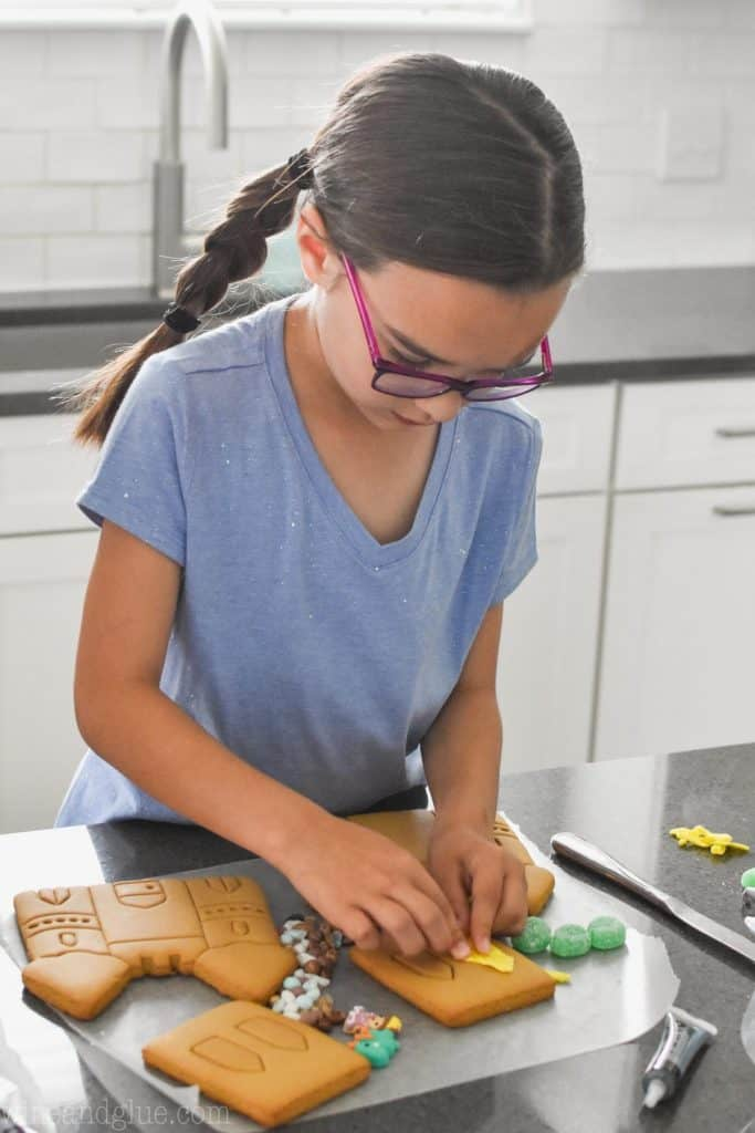 little girl with glasses and braids decorating a cookie castle with yellow fondant