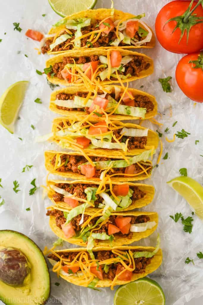 overhead view of hard shell tacos (8 in a row), filled with taco meat recipe and topped with lettuce, tomatoes, and cheese