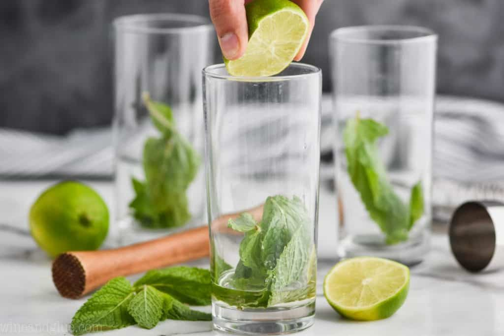 three high ball glasses with mint in them and a lime being squeezed into the first one to make a mojito drink
