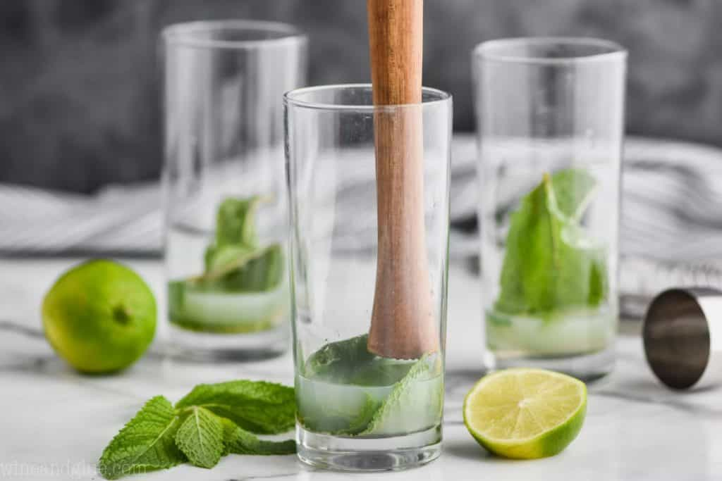 three high ball glasses with mint and lime juice and simple syrup in them and the first glass has a wood muddler about to muddle the ingredients for a mojito