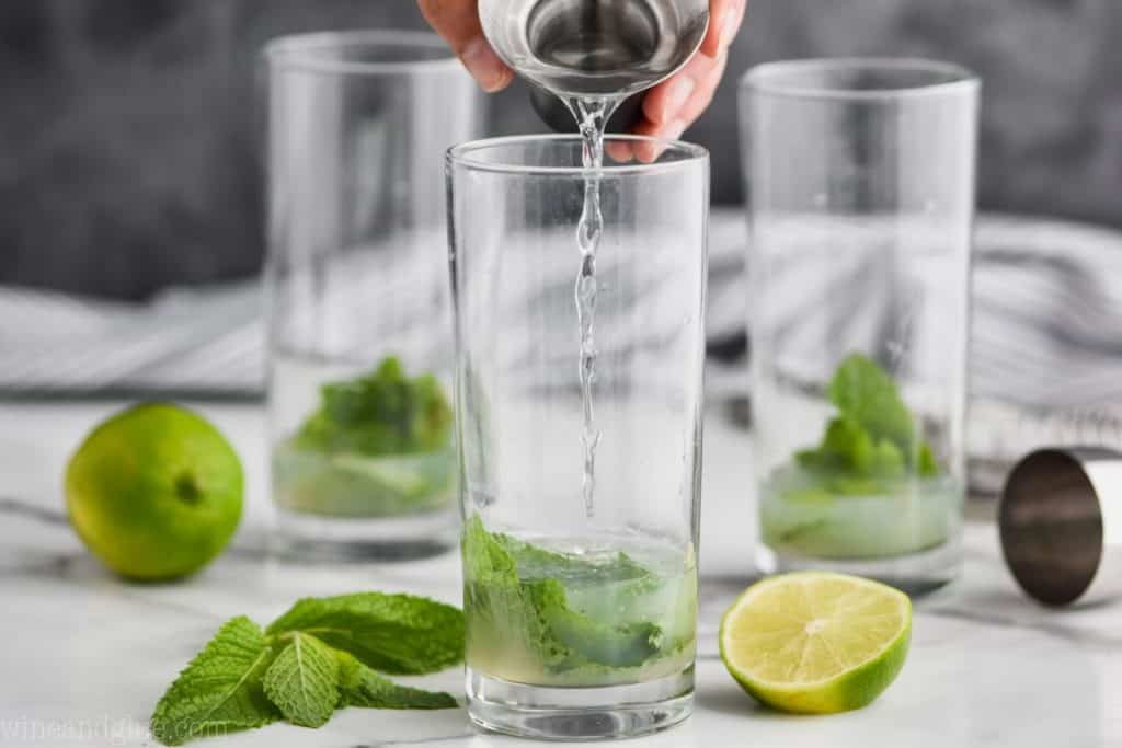 three high ball glasses with muddled mint and lime juice in them to make a mojito recipe and white rum being poured in the first glass