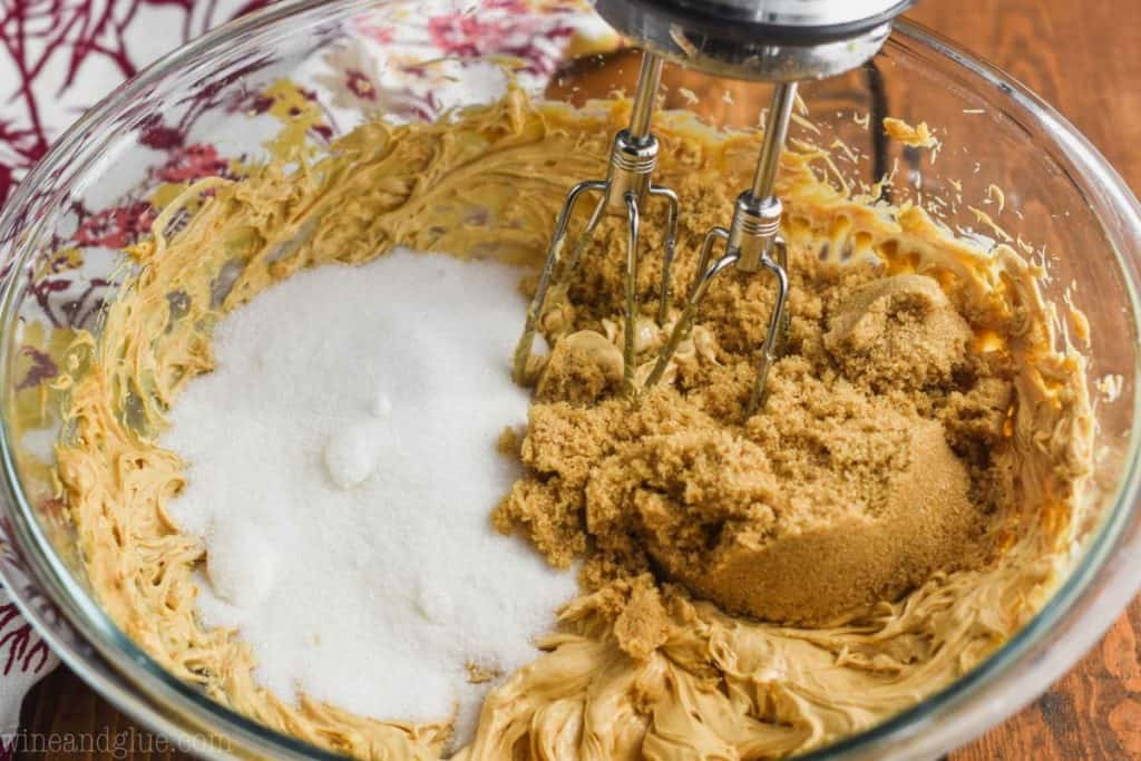 white and brown sugar being added to the batter of pumpkin peanut butter cookies with the beaters of a hand mixer being put into the bowl