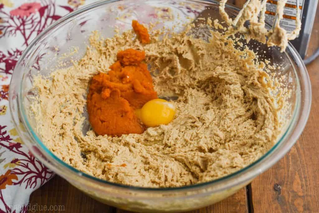 pumpkin puree and an egg yolk being added to pumpkin peanut butter cookie batter in a large glass bowl