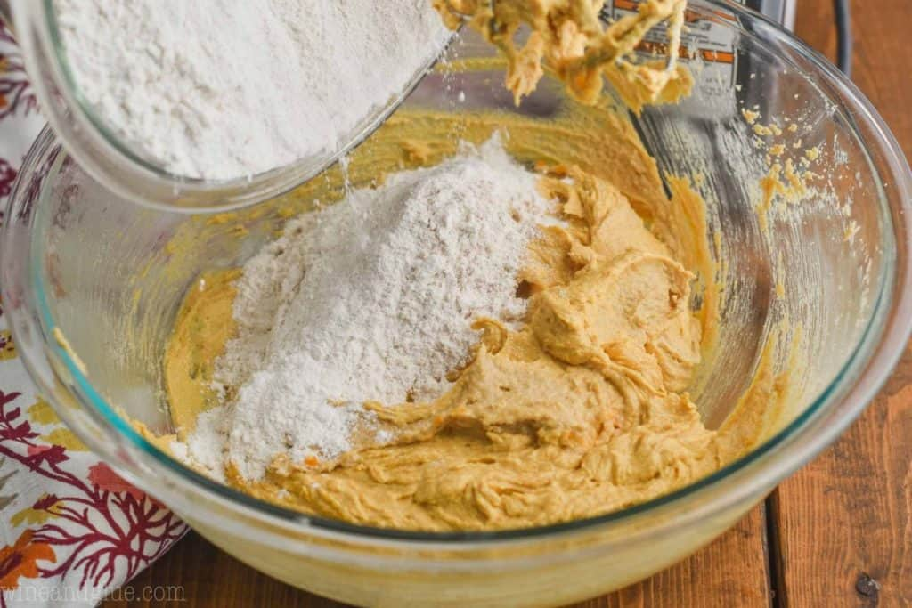 flour being poured into a bowl of pumpkin peanut butter cookie batter