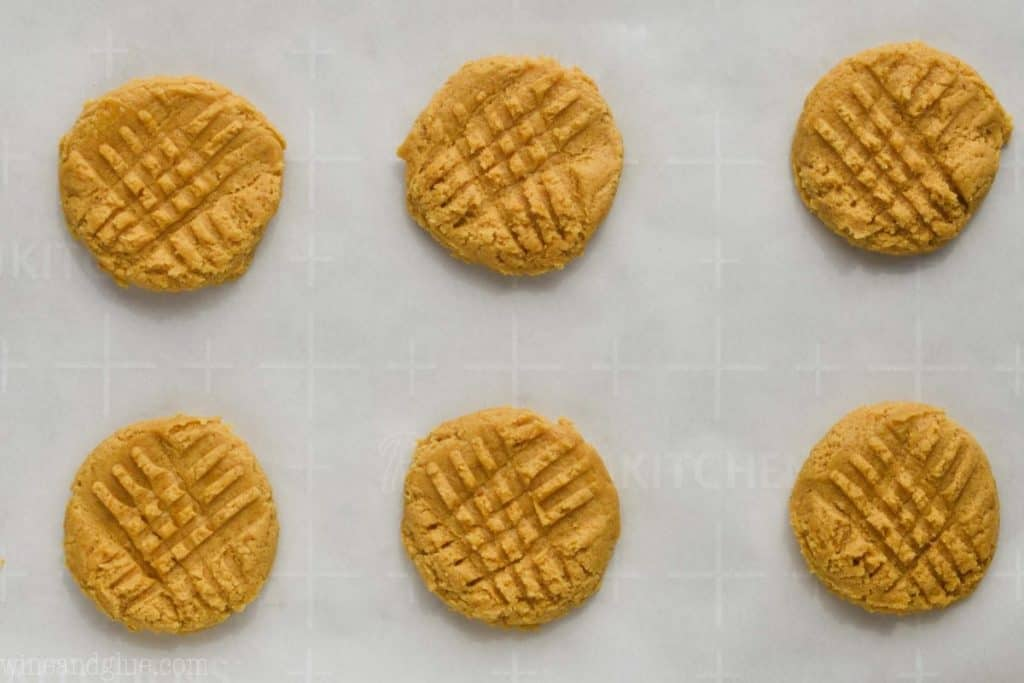 six pumpkin peanut butter cookies on parchment paper ready to be baked