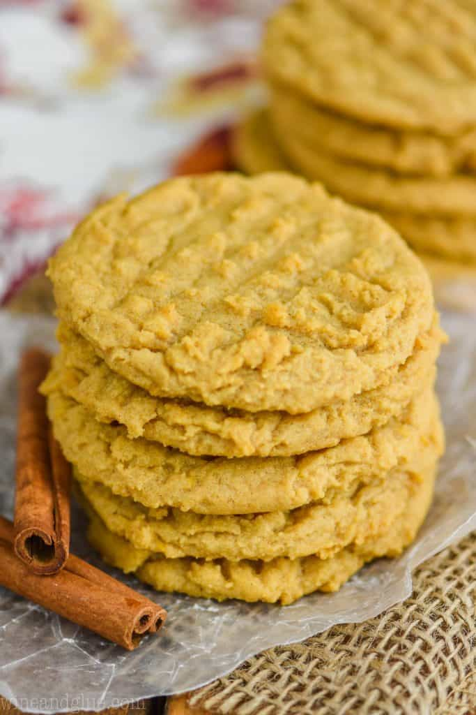a stack of pumpkin peanut butter cookies on wax paper with burlap underneath, cinnamon sticks next to them, another stack in the background