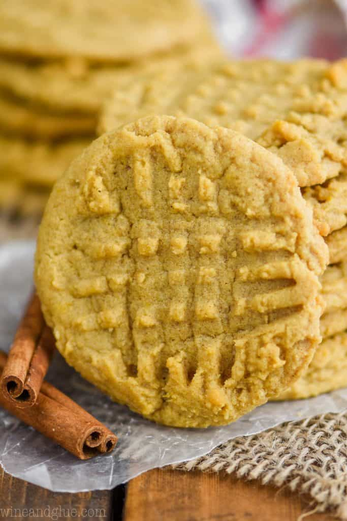 front view of a pumpkin peanut butter cookie as it leans against a stack of cookies, a second stack in the background