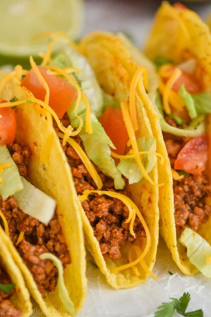 close up view of a taco made with homemade taco meat recipe and topped with chopped lettuce, tomatoes, and shredded cheese