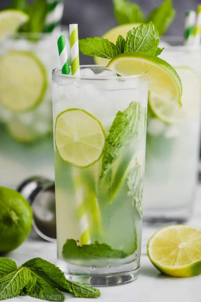 up close view of a high ball glass filled with a mojito cocktail, lime slices, fresh mint, striped green straws, and garnished with lime wedges and fresh mint