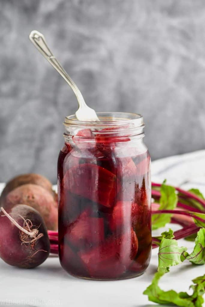 fork sticking out of an open mason jar of pickled quick pickled beets on a white surface against a gray background