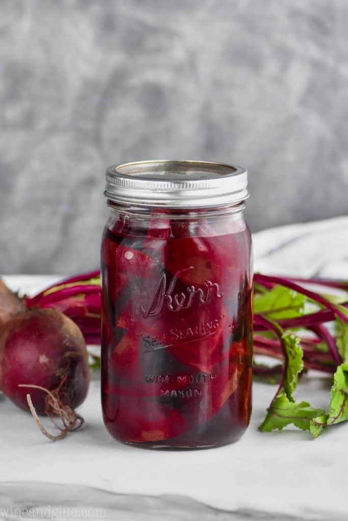 mason jar on a white surface against a gray background filled with pickled beets recipe