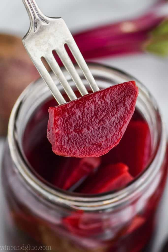 quick pickled beet on a fork over a jar of them