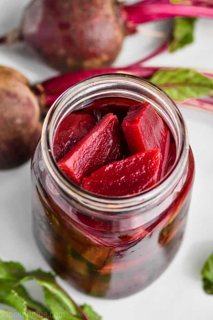 overhead view of a mason jar with pickled beets in it and raw beets laying next to it