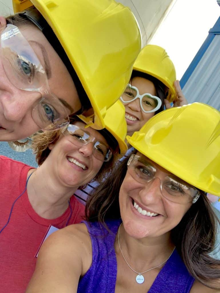 four women in hard hats and protective eye wear