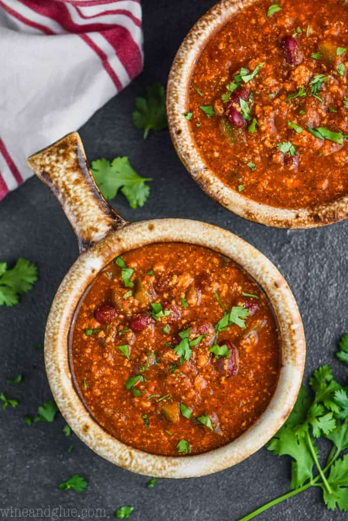 overhead view of a brown bowl with a handle holding vegetarian bean chili recipe garnished with cilantro on a dark surface with more cilantro around it