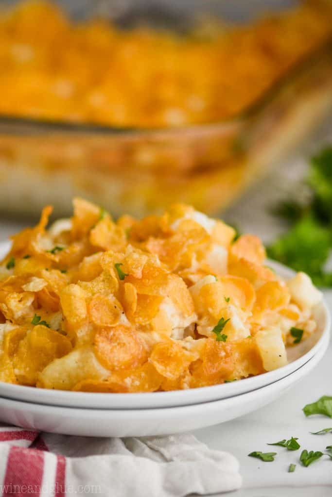 up close photo of two stacked white plates that have been topped with cheesy potatoes and garnished with small bits of parsley, a clear baking dish in the background