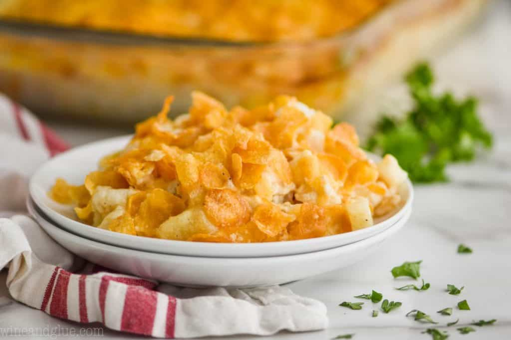 landscape photo of two plates with a pile of cheesy potato recipe, garnished with parsley and clear baking dish in the background