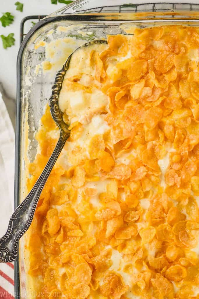 overhead view of a clear baking dish filled with cheesy potatoes with corn flakes with a spoon going into it