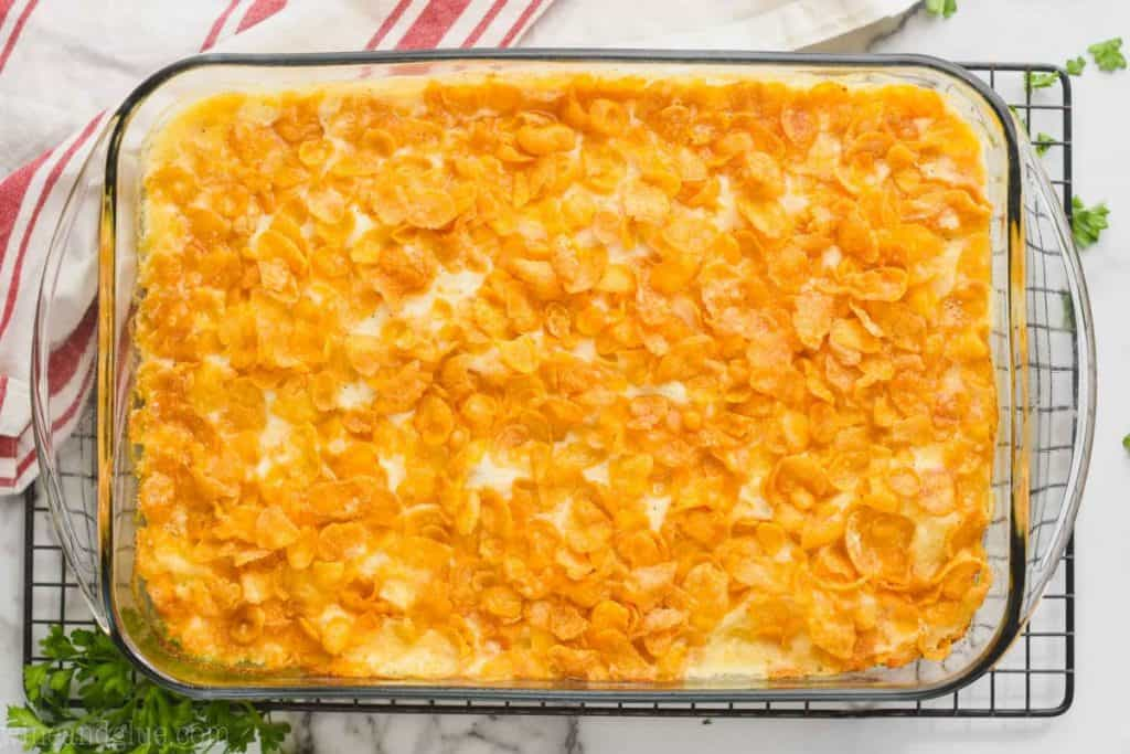 landscape photo of an overhead view of a clear baking dish on a wire cooling rack filled with cooked cheesy potato recipe, lots of crisp cornflakes on top
