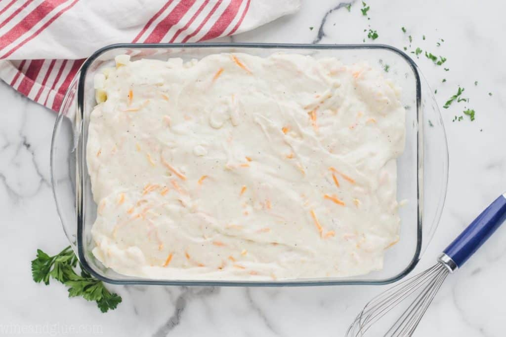 clear baking dish on a white surface filled with creamy substance and pieces of shredded cheese visible to make cheesy potatoes casserole