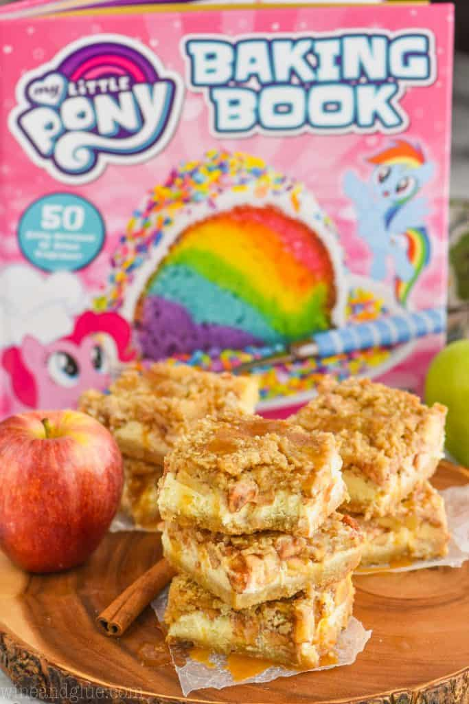 stacked apple cheesecake bars on a wood platter with the my little pony baking book in the background