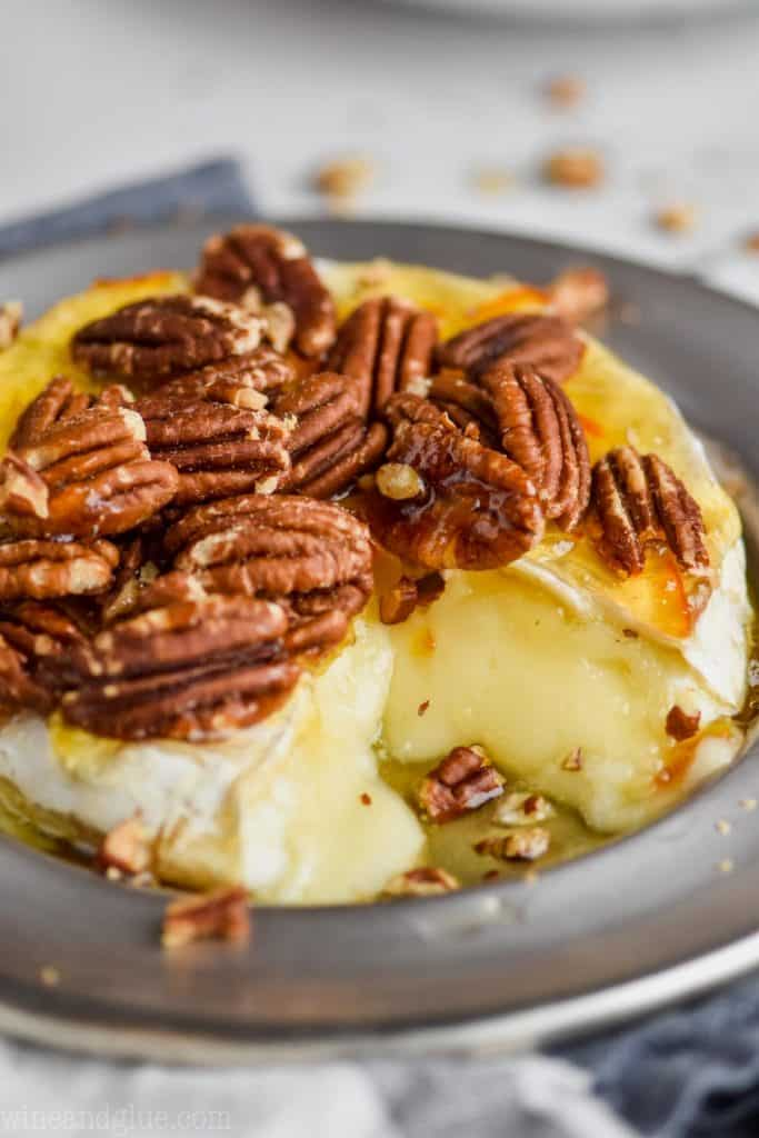 close up picture of baked brie recipe made with honey, pecans, and marmalade