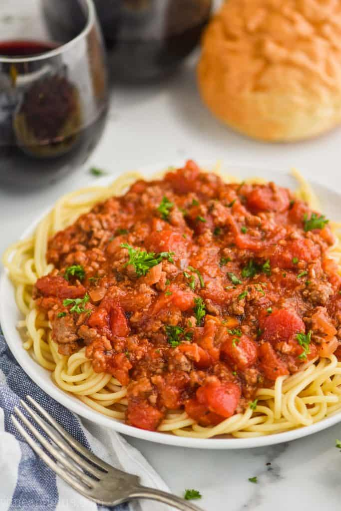 white plate with spaghetti topped with spaghetti meat sauce recipe, two red wines and bread in the background, fork in the foreground