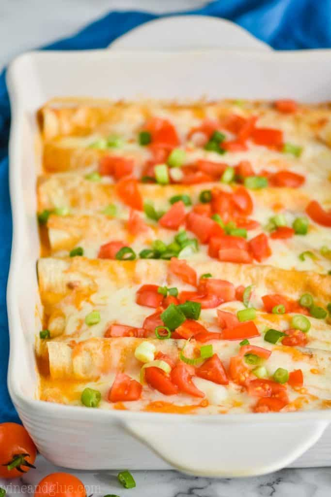 side view of a chicken enchilada casserole in a white ceramic baking dish, enchiladas are buffalo flavored and garnished with chopped tomatoes and green onions