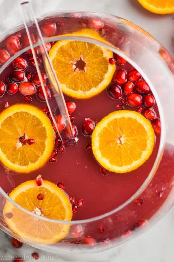 overhead view of a sphere punch bowl full of christmas punch with orange slices and cranberries floating in it