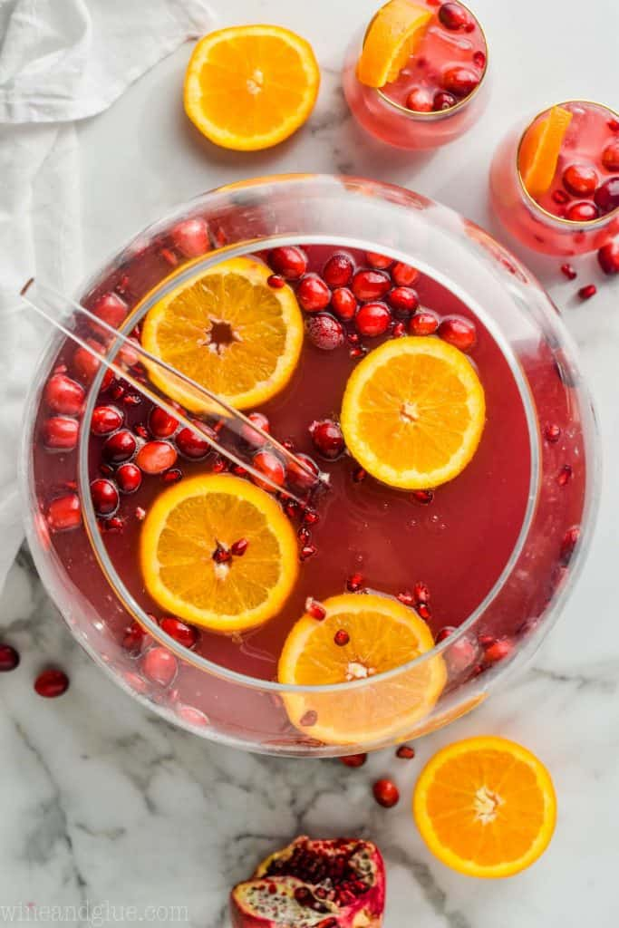 overhead view of sphere punch bowl with non alcoholic Christmas punch with orange slices and cranberries floating in it and two glasses full of it
