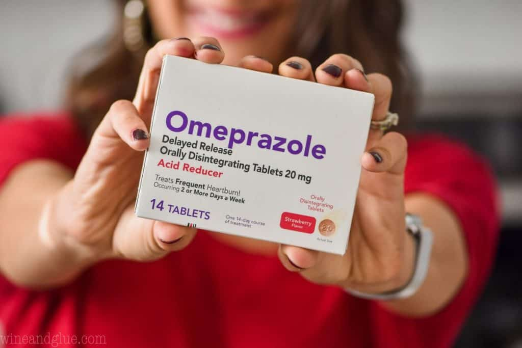 a woman's hands (with the woman blurred in the background) holding a box of omeprazole