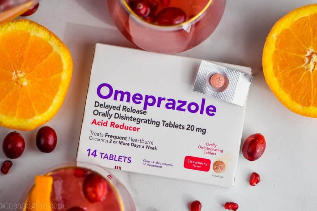 overhead view of a box of omeprazole with one pill tablet on top and ingredients for holiday punch around it