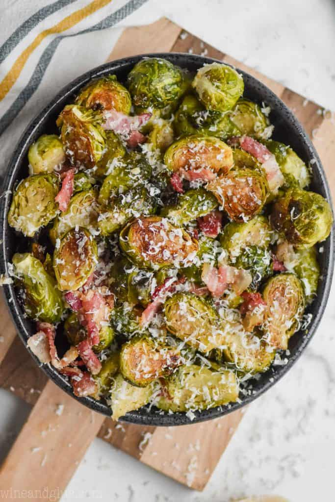 overhead view of a black bowl on a cutting board filled with roasted brussels sprouts with bacon