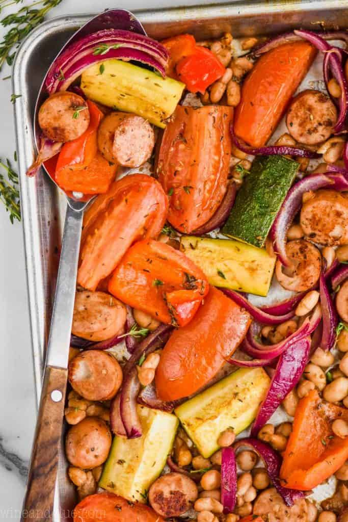 overhead view of a spoon in a pan of sausage, beans and roasted vegetables to make a sheet pan dinner