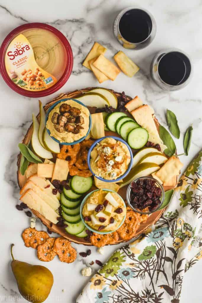 overhead view of a hummus charcuterie board made with sabra hummus, two wine glasses off to the side and whole pear