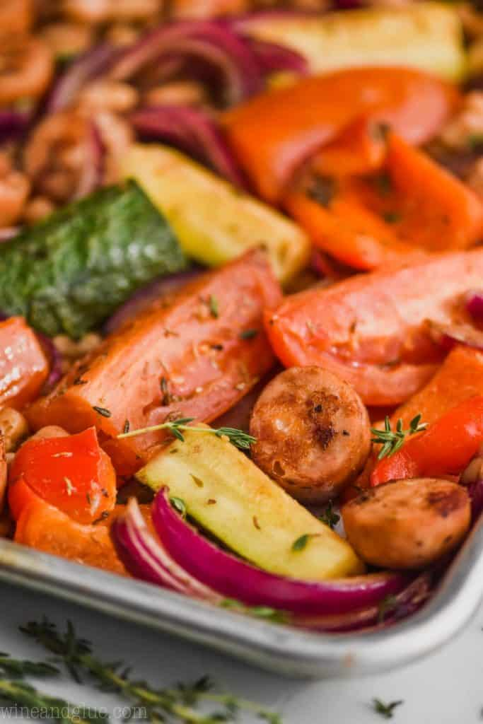 up close view of sausage and veggie sheet pan dinner recipe with zucchini, tomatoes, peppers, cut chicken sausages and red peppers on a rimmed baking sheet