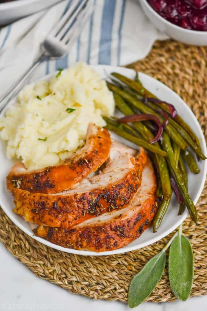 cut up baked turkey breast on a plate with mashed potatoes and green beans