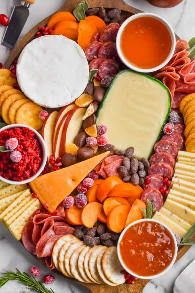 overhead view of a charcuterie board with four types of cheese, three types of crackers, persimmons, pears, oranges, and three types of spread