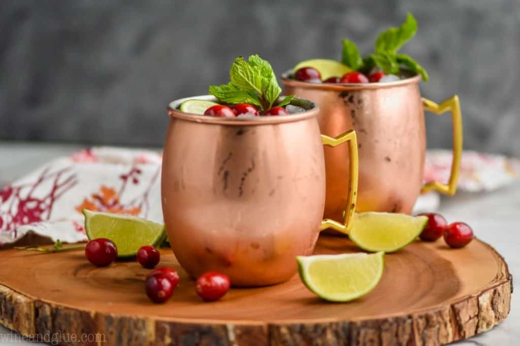 horizontal photo of two copper mugs on a wood platter with some fresh cranberries and lime wedges