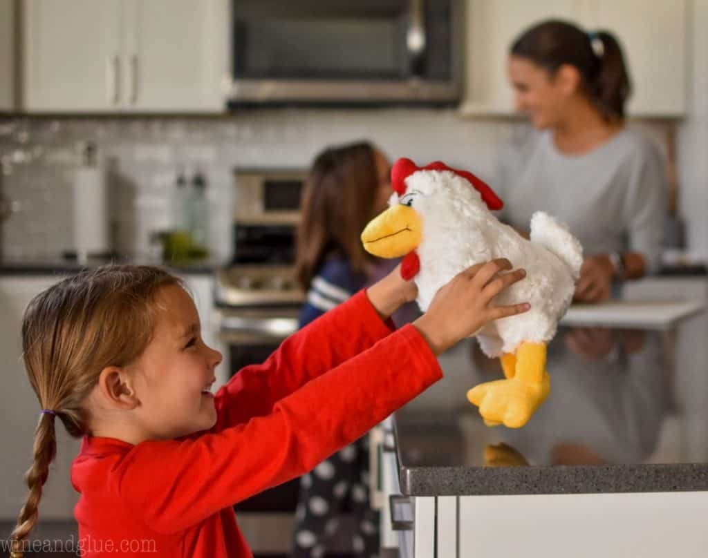 picture of a little girl in a kitchen playing with a stuffed chicken