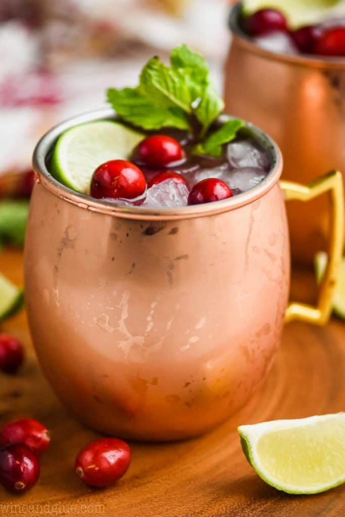 close upon a copper mug that is full to the brim with cranberry moscow mule, garnished with fresh cranberries, a lime wedge, and a sprig of fresh mint