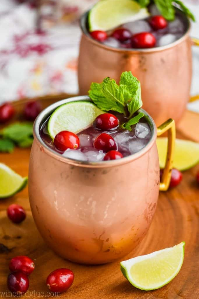 two copper mugs full of cranberry moscow mule recipe on a wooden tray, full of ice, and garnished with fresh cranberries, a lime wedge and mint sprigs