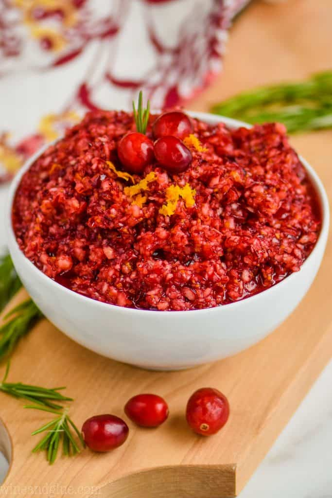 a white bowl full of cranberry relish recipe on a cutting board, garnished with three cranberries, orange zest, and a little rosemary