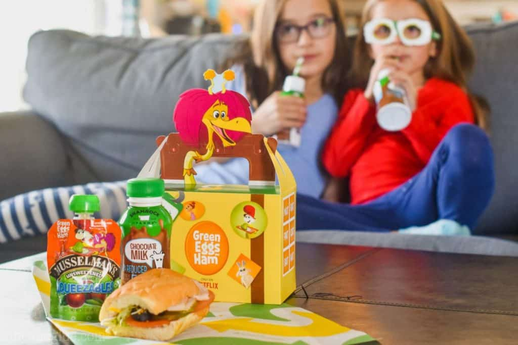 Two girls on a couch in the background. In the foreground, the Subway Fresh Fit for Kids meal is there with a sandwich, Squeezable, and chocolate milk