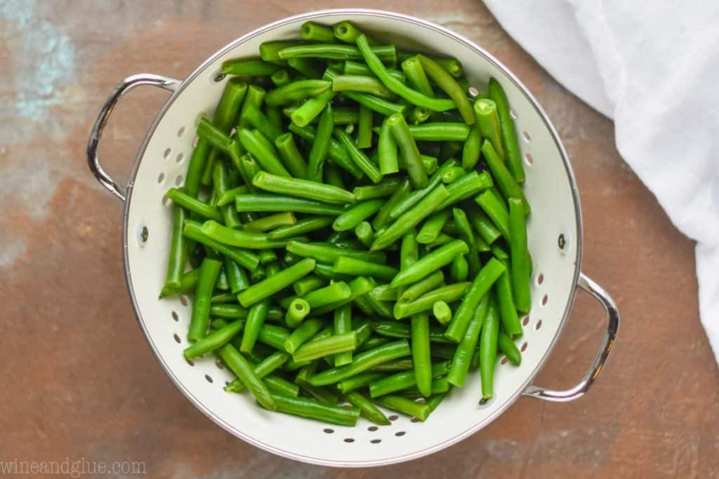 overhead photo of green beans that have been par boiled in a white metal colander