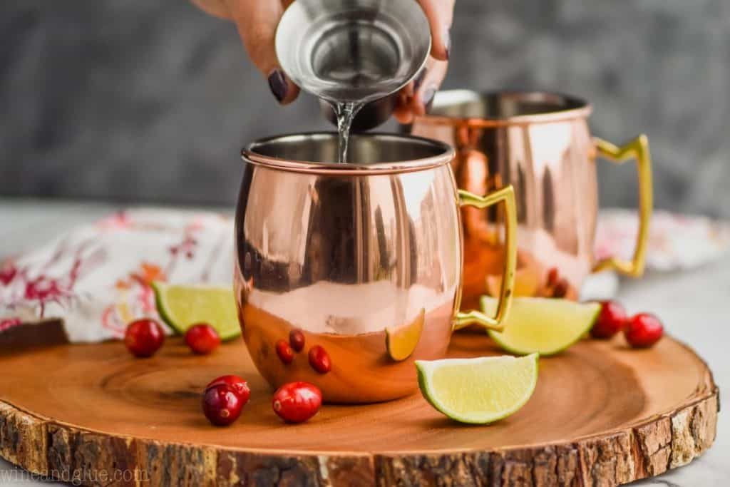 landscape photo of a hand pouring vodka into a copper mug to make cranberry moscow mules