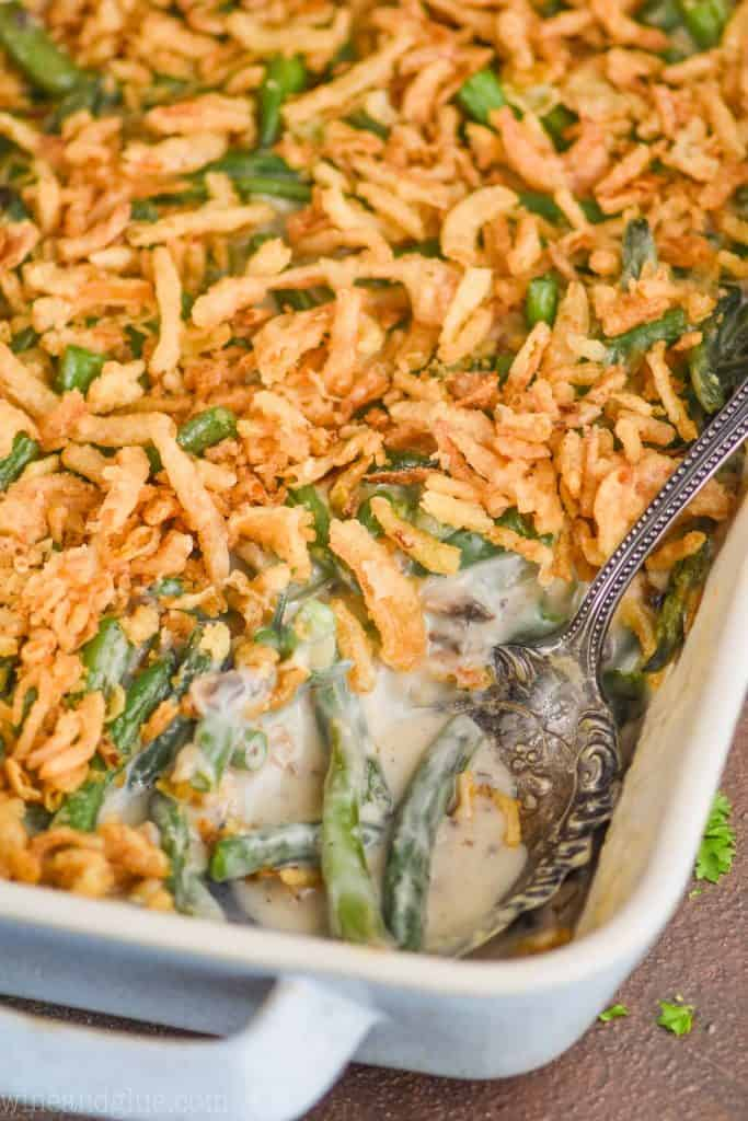 an antique spoon dishing into a casserole dish of green bean casserole recipe