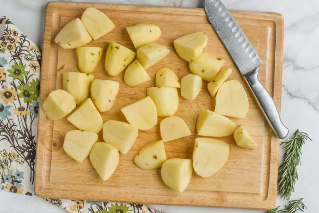 overhead of a wooden cutting board with potatoes that have been peeled and quartered
